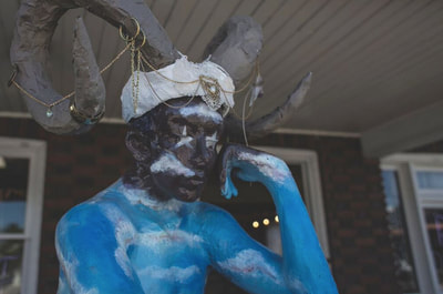 Horned statue display at Black Hole Body Piercing